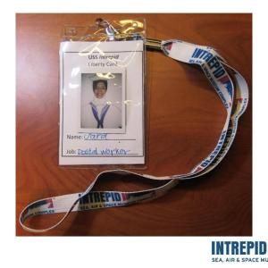 A wearable badge from the Intrepid Sea, Air, and Space Museum that includes a photograph of a person and her name and job with a lanyard attached
