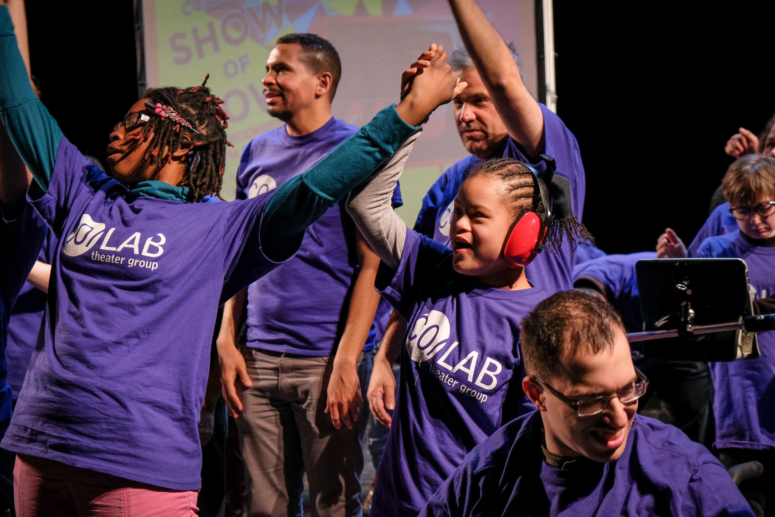 Seven actors of various ages wear purple CO/LAB shirts. Each is looking in a different direction, several have arms raised.