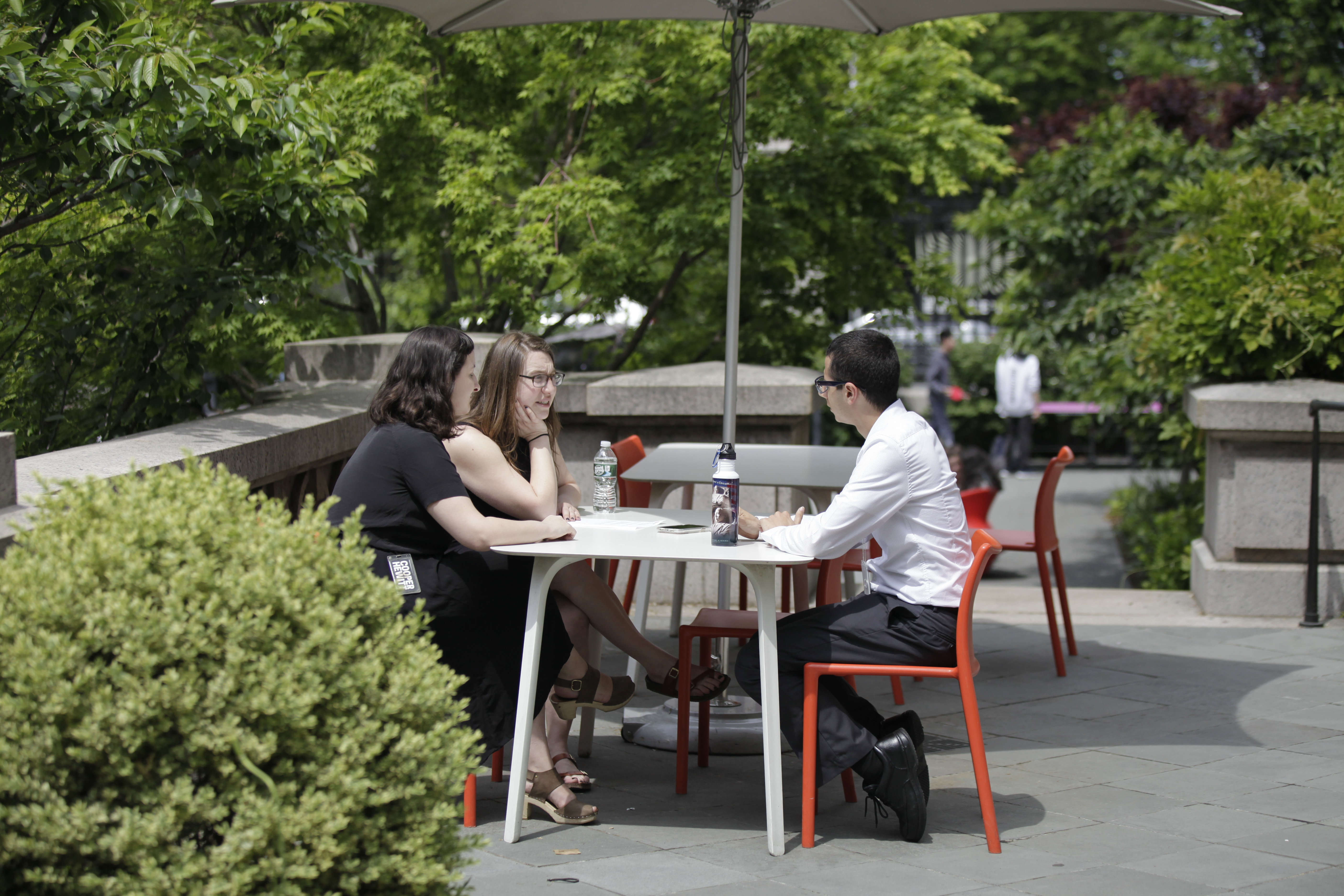Three people sit at a table under an umbrella in the Cooper Hewitt garden