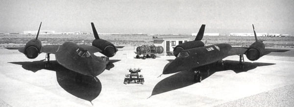 This black and white image features two sleek, black airplanes at rest on a runway. The airplanes look very similar to each other. The aircraft on the left is the SR-71 Blackbird and the aircraft on the right is the A-12.