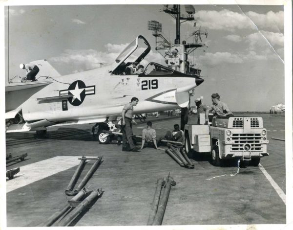 In this black and white photograph there is a large white aircraft on the flight deck of the Intrepid. Tools are on the ground and six sailors are attaching a small tractor to the airplane.