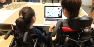 two wheelchair users work together on a computer