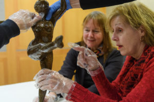 three visitors feel a bronze sculpture