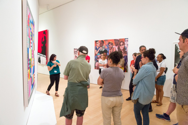 A group of visitors stand in a brightly lit gallery watching a gallery guide signing about a colorful painting