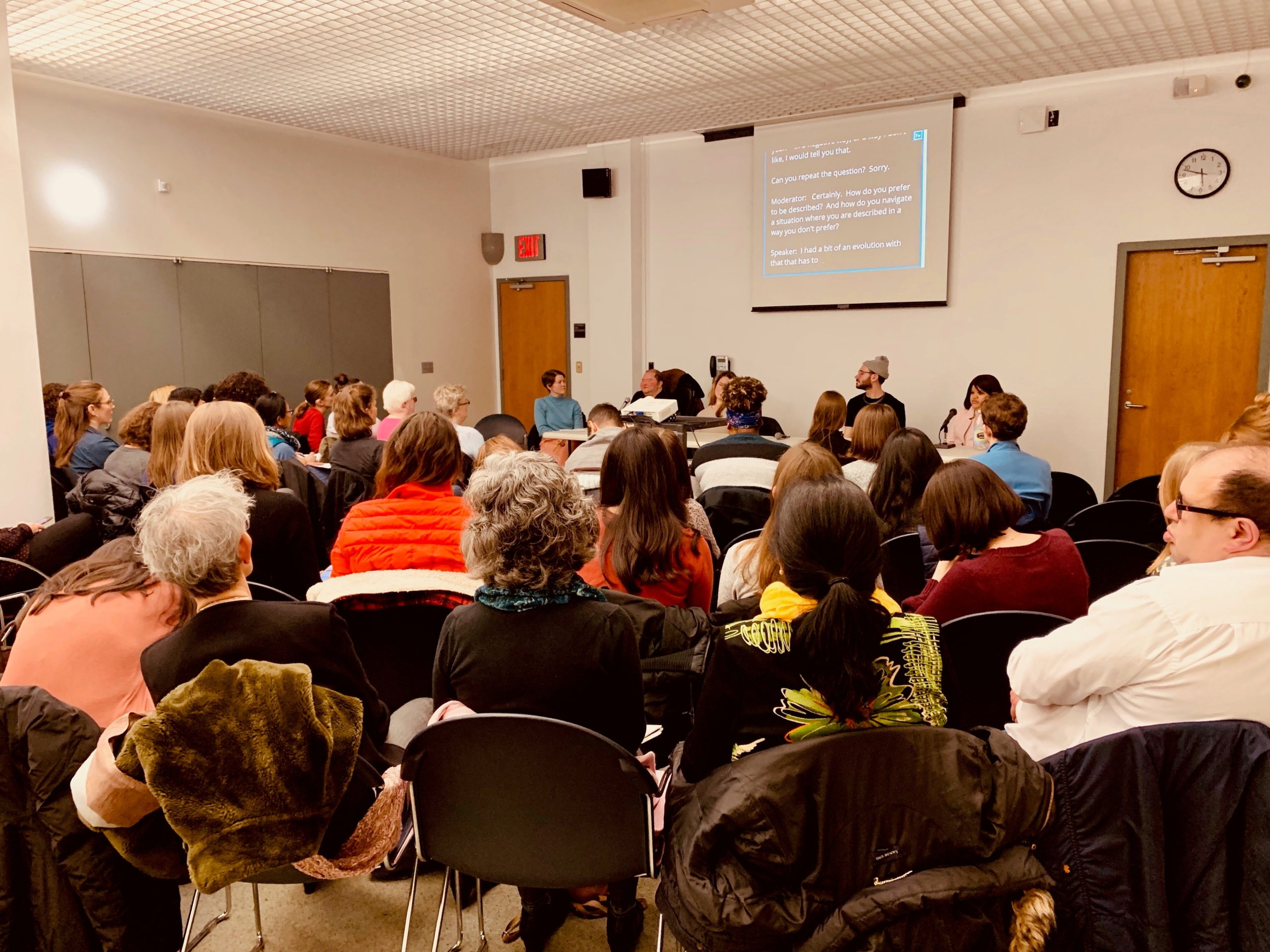 In the foreground an audience attends a panel conversation on mindful communication. Four panelists sit at a table in the background.