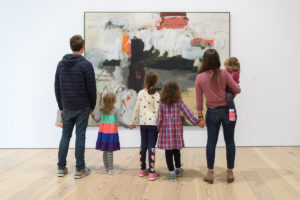 A family views an artwork in a gallery.