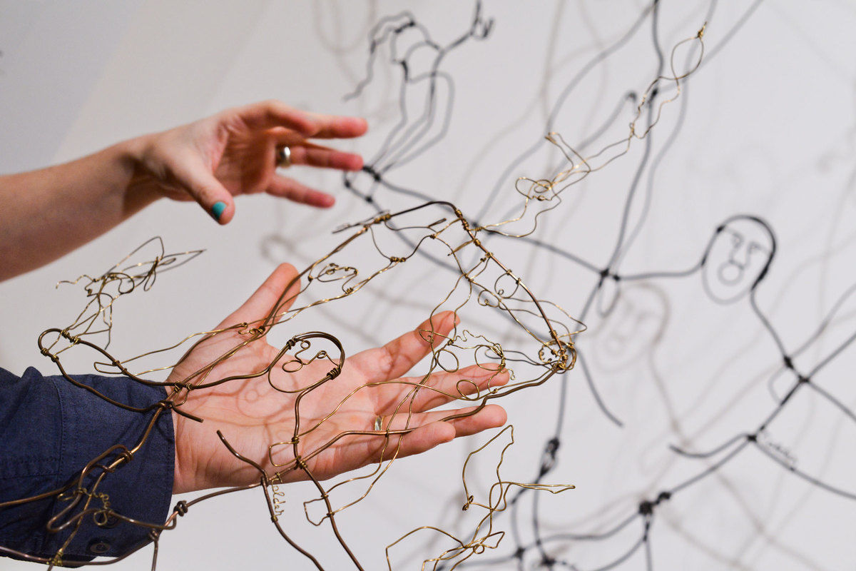 Hands interact with a wire sculpture in front of a white wall.