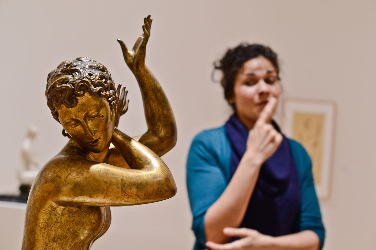 An educator communicates in ASL about a gold sculpture of a woman.