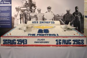 Photo of full-size reproduction of Intrepid's giant 25th anniversary cake with life-size photos of crew members behind it