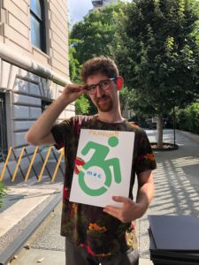 Person poses with their disability pride poster.
