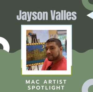 Jayson Valles looking at the camera, wearing a red shirt, with sunglasses hanging from the collar of his shirt. His painting of a city landscape at night is on an easel behind him.