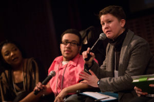 2 people sit holding microphones; 1 of them is speaking. A 3rd person looks on.